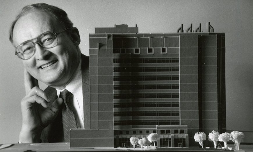 Dr. Bluemle smiling with a model version of the Bluemle Life Sciences Building